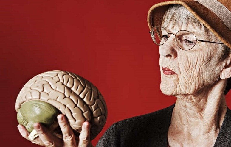 Senior Woman Holding Brain In Hand